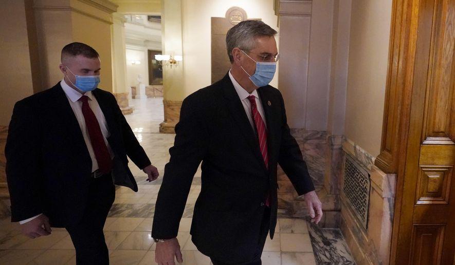 Georgia Secretary of State Brad Raffensperger, right, walks to his office in the Capitol Building Monday, Jan. 4, 2021, in Atlanta. (AP Photo/John Bazemore)