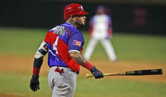 Puerto Rico's Yadier Molina walk to first base after hit by pitch during the first inning of the team's' Caribbean Series baseball final game against the Dominican Republic at Teodoro Mariscal stadium in Mazatlan, Mexico, Saturday, Feb. 6, 2021. (AP Photo/Moises Castillo)