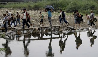 FILE - In this April 14, 2019 file photo, Venezuelans cross illegally into Colombia near the Simon Bolivar International Bridge, seen from La Parada near Cucuta, Colombia. President Ivan Duque said on Wednesday, Feb. 3, 2021, that Colombia needs greater cooperation from the international community to carry out a vaccination plan against COVID-19 for the estimated  million Venezuelan migrants without documents who are in the country, who are so far excluded from the new coronavirus vaccination plan. (AP Photo/Fernando Vergara, File)