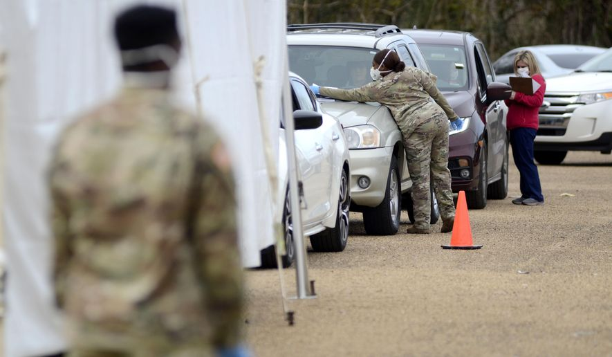 Mississippi National Guard and state department of health officials assist people waiting in line to receive COVID-19 vaccinations at a drive-thru vaccination set up at the Pike County Health Department in McComb, Miss., on Wednesday, Jan. 6, 2021. (Matt Williamson/The Enterprise-Journal via AP)