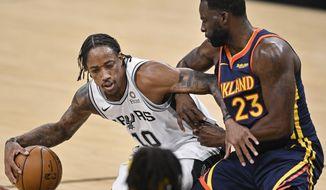San Antonio Spurs' DeMar DeRozan (10) drives against Golden State Warriors' Draymond Green during the first half of an NBA basketball game, Monday, Feb. 8, 2021, in San Antonio. (AP Photo/Darren Abate)