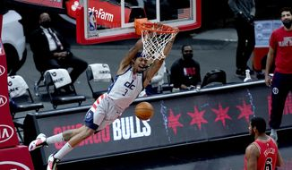 Washington Wizards' Bradley Beal (3) dunks the ball as Chicago Bulls' Cristiano Felicio watches during the first half of an NBA basketball game Monday, Feb. 8, 2021, in Chicago. (AP Photo/Charles Rex Arbogast)