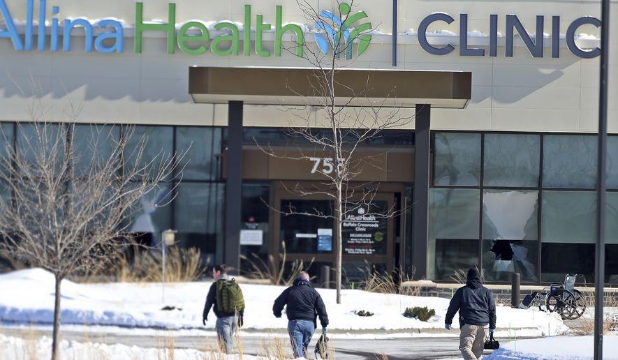 Law enforcement personnel walk toward the Allina Health clinic, Tuesday, Feb. 9, 2021, in Buffalo, Minn. Authorities say multiple people were shot at the Minnesota health clinic on Tuesday and someone was taken into custody afterward. (David Joles/Star Tribune via AP)