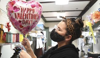 Carolyn Beaudreau blows up a helium balloon with Valentine's Day theme at Mount Williams Greenhouses in North Adams, Mass on Tuesday, Feb. 9, 2021, as area florists get ready for the busy Valentine's Day weekend. (Gillian Jones/The Berkshire Eagle via AP)