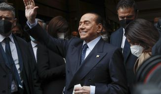 Former Italian Premier Silvio Berlusconi waves to reporters as he arrives at the Chamber of Deputies to meet Mario Draghi, in Rome, Tuesday, Feb. 9, 2021. Former European Central Bank chief Draghi is consulting Italy's fractious parties after being tapped by President Sergio Mattarella to try to pull together a government to guide the debt-riddled country through the health and economic crises it is confronting. (AP Photo/Alessandra Tarantino)