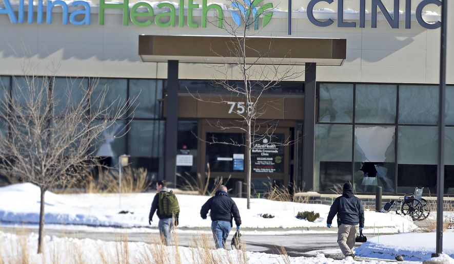 Law enforcement personnel walk toward the Allina Health clinic, Tuesday, Feb. 9, 2021, in Buffalo, Minn. Authorities say multiple people were shot at the Minnesota health clinic on Tuesday and someone was taken into custody afterward. (David Joles/Star Tribune via AP)