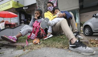 Venezuelan migrant Katerine Valero, 29, and her children Dariusca, 8, left, and Wilkerson, 4, rest outside a strip mall, in Bogota, Colombia, Tuesday, Feb. 9, 2021. Colombia said Monday it will register hundreds of thousands of Venezuelan migrants and refugees currently in the country without papers, in a bid to provide them with legal residence permits and facilitate their access to health care and legal employment opportunities. (AP Photo/Fernando Vergara)