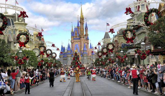 In this Dec. 21, 2020, file photo, crowds line Main Street USA, with Cinderella Castle on the horizon, to watch characters parade at the Magic Kingdom at Walt Disney World, in Lake Buena Vista, Fla. (Joe Burbank/Orlando Sentinel via AP, File)