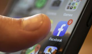 In this Aug. 11, 2019, file photo, an iPhone displays the Facebook app in New Orleans. (AP Photo/Jenny Kane, File)