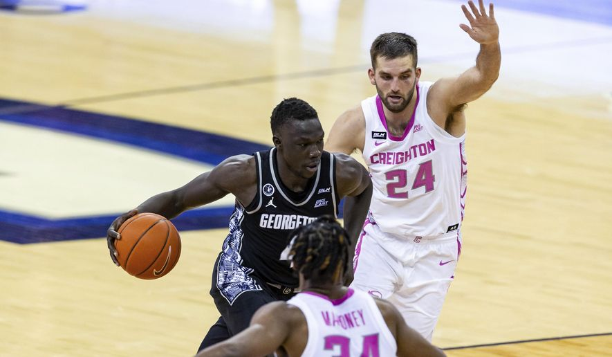 Georgetown forward Chudier Bile (4) drives the basket against Creighton guard Mitch Ballock (24) and guard Denzel Mahoney (34) during the second half of an NCAA college basketball game Wednesday, Feb. 3, 2021, in Omaha, Neb. (AP Photo/John Peterson) **FILE**
