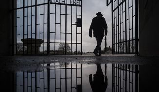 File - In this Sunday, Jan. 27, 2019 file photo a man walks through the gate of the Sachsenhausen Nazi death camp with the phrase 'Arbeit macht frei' (work sets you free) during International Holocaust Remembrance Day in Oranienburg, about 30 kilometers (18 miles), north of Berlin, Germany. German prosecutors say they have charged a 100-year-old man with 3,518 counts of accessory to murder on allegations he served as an SS guard at the Nazis' Sachsenhausen concentration camp on the outskirts of Berlin. (AP Photo/Markus Schreiber, file)