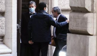 Mario Draghi, right, arrives at the Chamber of Deputies in Rome, Monday, Feb. 8, 2021. Former European Central Bank chief Draghi is consulting Italy's fractious parties after being tapped by President Sergio Mattarella to try to pull together a government to guide the debt-riddled country through the health and economic crises it is confronting. (Mauro Scrobogna/LaPresse via AP)