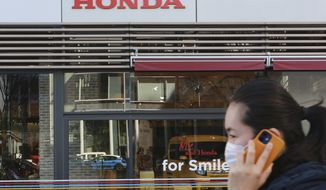 A woman wearing a face mask walks in front of a Honda Motor Co. showroom in Tokyo, Tuesday, Feb. 9, 2021. Japanese automaker Honda reported Tuesday its fiscal third quarter profit more than doubled to 284 billion yen ($2.7 billion) despite the coronavirus pandemic as auto sales grew in Japan and the U.S. (AP Photo/Koji Sasahara)