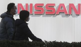 People walk past the corporate logo at Nissan Motor Co.'s global headquarters in Yokohama, near Tokyo, Tuesday, Feb. 9, 2021. Japanese automaker Nissan reported Tuesday losses for the fiscal third quarter, as its sales were hit by the coronavirus pandemic and its brand image continued to take a beating from the financial misconduct scandal centered on its former chairman, Carlos Ghosn. (AP Photo/Koji Sasahara)