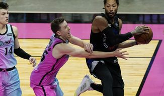 New York Knicks guard Derrick Rose looks to pass the ball as Miami Heat guard Duncan Robinson (55) defends during the first half of an NBA basketball game, Tuesday, Feb. 9, 2021, in Miami. (AP Photo/Marta Lavandier)