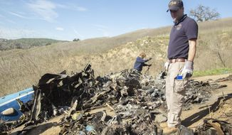 FILE - In this Jan. 27, 2020, file photo, provided by the National Transportation Safety Board, NTSB investigators Adam Huray, right, and Carol Hogan examine wreckage as part of the NTSB's investigation of a helicopter crash near Calabasas, Calif. Federal safety officials are expected to vote Tuesday, Feb. 9, 2021, on what likely caused the helicopter carrying Kobe Bryant, his 13-year-old daughter and seven others to crash into a Southern California hillside last year, killing all aboard. (James Anderson/National Transportation Safety Board via AP, File)