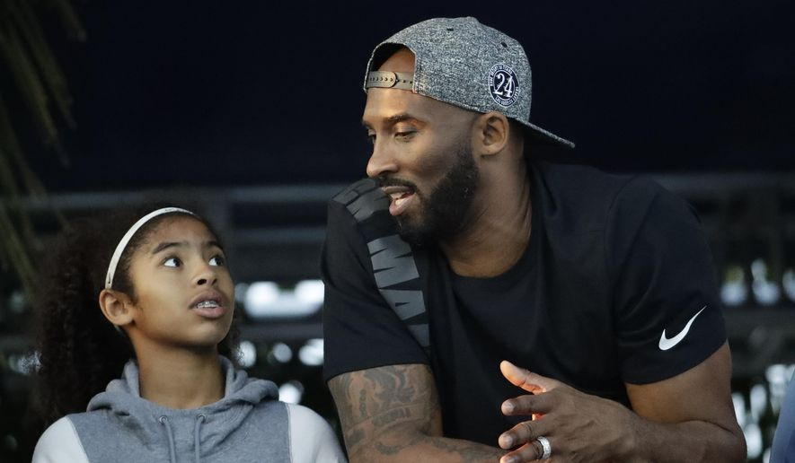 In this July 26, 2018, file photo, former Los Angeles Laker Kobe Bryant and his daughter Gianna watch the U.S. national championships swimming meet in Irvine, Calif. Federal safety officials are expected to vote Tuesday, Feb. 9, 2021, on what likely caused the helicopter carrying Kobe Bryant, his 13-year-old daughter and seven others to crash into a Southern California hillside last year, killing all aboard. (AP Photo/Chris Carlson, file) **FILE**