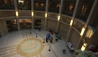 A man walks on the second floor of the New Mexico State Capitol building while emergency medical technicians wait to administer COVID-19 tests on Monday, Feb. 8, 2021, in Santa Fe, New Mexico. The building was closed to the public at the start of the pandemic. State leaders are holding most meetings virtually, with routine testing offered to legislators, staff members and the media. (AP Photo/Cedar Attanasio)