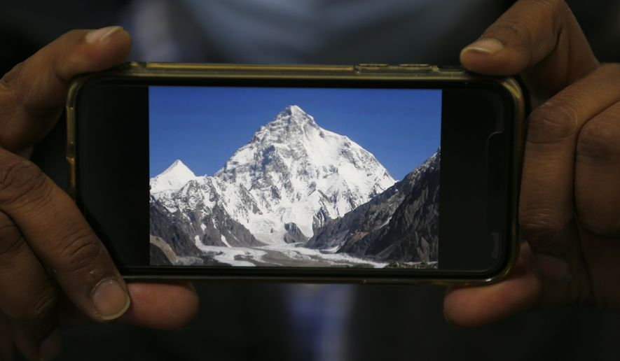 A photo of K2, the world's second-highest mountain, is displayed on a cell phone in Islamabad, Pakistan, Tuesday, Feb. 9, 2021. Families of the three mountaineers who went missing in Pakistan last week while attempting to scale K2 are growing more desperate on Tuesday, a day after bad weather halted the search for the climbers. (AP Photo/Anjum Naveed)