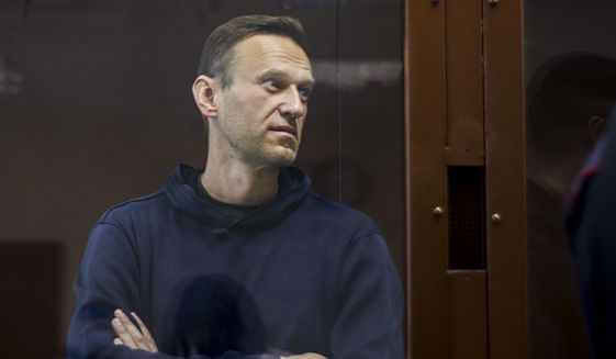 """In this photo provided by the Babuskinsky District Court, Russian opposition leader Alexei Navalny stands in a cage during a hearing on his charges for defamation, in the Babuskinsky District Court in Moscow, Russia, Friday, Feb. 5, 2021. Russian opposition leader Alexei Navalny appeared in a Moscow court on Friday for the second time this week, this time on a charge of slandering a World War II veteran. The politician, who was ordered earlier this week to serve two years and eight months in prison, slammed the hearing as a """"disgusting PR trial"""" intended by the Kremlin to disparage him. (Babuskinsky District Court Press Service via AP)"""
