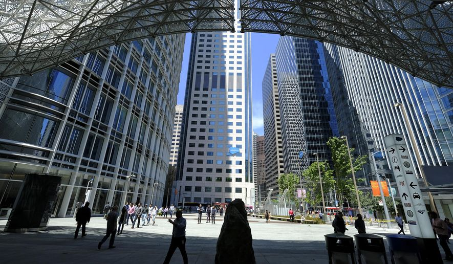 FILE - In this Monday, July 1, 2019, file photo, people make their way into the Salesforce Transit Center after it reopened, in San Francisco. San Francisco-based business software maker Salesforce says it will let most of its employees work remotely even after the pandemic, at least for part of the week. (AP Photo/Eric Risberg, File)
