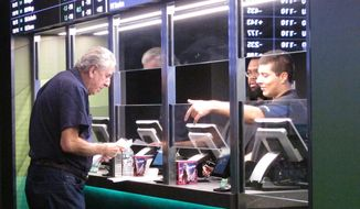 In this Oct. 8, 2019, file photo, a man makes a sports bet at Resorts casino in Atlantic City, N.J. Sports books say the blitz of advertising they launched in the run up to the 2021 Super Bowl, while costly, paid off in terms of attracting new customers to the fast-growing legal sports betting industry in the U.S. (AP Photo/Wayne Parry, File) **FILE**