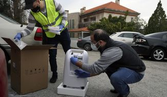 Members of Lebanese NGO Baytna Baytak Firas Minnawi, right, and Mario Suleiman, left, unpack oxygen machine to be donated to an elderly COVID-19 patient in Beit Shebab, a mountain village 15 mile (24 km) north of Beirut, Lebanon, Wednesday, Jan. 27, 2021. The group of Lebanese activists are matching empty apartments and hotel rooms with nurses and doctors who are serving countless hours in the country's hospitals overwhelmed with COVID patients and who need a place to rest without endangering their families or elderly parents. (AP Photo/Bilal Hussein)