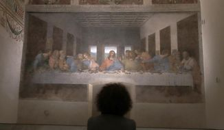 A woman admires Leonardo da Vinci's painting ' The Last Supper ', dating back to 1494-1498 and preserved at the ex-Renaissance refectory of the convent adjacent to the sanctuary of Santa Maria delle Grazie church, in Milan, Italy, Tuesday, Feb. 9, 2021. 'Last Supper' reopened Tuesday to the public after closure due to COVID-19 lockdown measures. (AP Photo/Antonio Calanni)