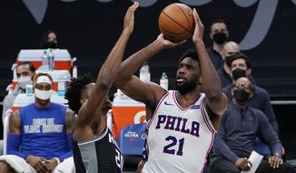 Sacramento Kings center Hassan Whiteside, left, tries to block the shot of Philadelphia 76ers center Joel Embiid, right, during the first half of an NBA basketball game in Sacramento, Calif., Tuesday, Feb. 9, 2021. (AP Photo/Rich Pedroncelli)