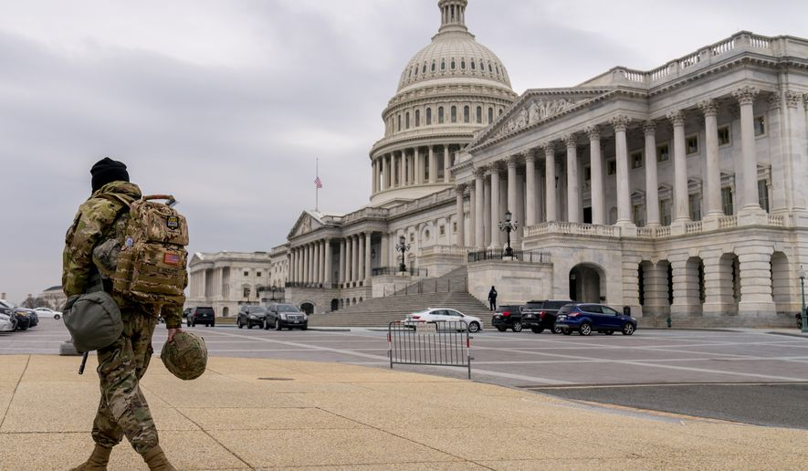 A member of the National Guard walks past the U.S. Capitol during the second impeachment trial of former President Donald Trump in Washington, Wednesday, Feb. 10, 2021. Trump was charged by the House with incitement of insurrection for his role in agitating a violent mob of his supporters that laid siege to the U.S. Capitol on Jan. 6, sending members of Congress into hiding as the Electoral College met to validate President Joe Biden's victory. (AP Photo/Andrew Harnik)