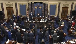 In this image from video, senators gather around Senate Majority Leader Chuck Schumer of N.Y., and House impeachment manager Rep. Jamie Raskin, D-Md., bottom left, after Sen. Mike Lee, R-Utah, made an objection to evidence presented by House impeachment managers during the second impeachment trial of former President Donald Trump in the Senate at the U.S. Capitol in Washington, Wednesday, Feb. 10, 2021. (Senate Television via AP)