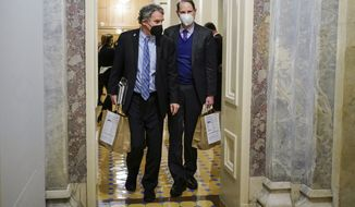 Sen. Sherrod Brown, D-Ohio and Sen. Ron Wyden, D-Or.,  walk the halls during a break in the second impeachment trial of former President Donald Trump, at the Capitol, Wednesday, Feb. 10, 2021 in Washington. (Joshua Roberts/Pool via AP)