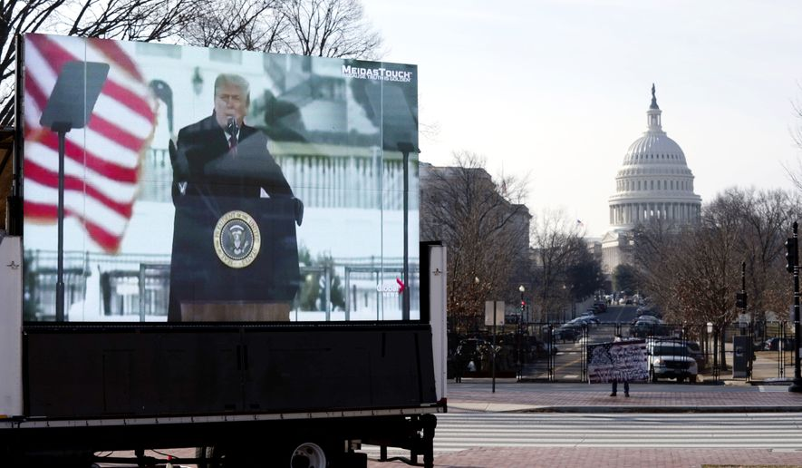 A photo of former President Donald Trump appears on a billboard truck parked near of the U.S. Capitol during the second impeachment trial of former President Trump, Wednesday, Feb. 10, 2021 on Capitol Hill in Washington.  (AP Photo/Jose Luis Magana)