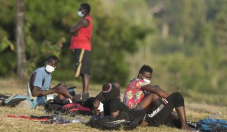 Haitian migrants sit on the grass at a migrant camp amid the new coronavirus pandemic in San Vicente, Darien province, Panama, Tuesday, Feb. 9, 2021. Panama is allowing hundreds of migrants stranded because of the pandemic, to move to the border with Costa Rica after just reopening its land borders. (AP Photo/Arnulfo Franco)