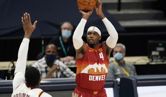 Denver Nuggets forward Paul Millsap, right, shoots over Cleveland Cavaliers center Andre Drummond in the first half of an NBAA basketball game Wednesday, Feb. 10, 2021, in Denver. (AP Photo/David Zalubowski)