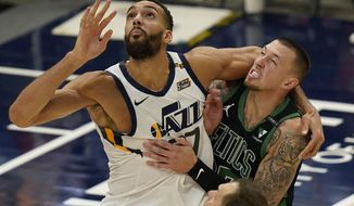 Utah Jazz center Rudy Gobert, left, and Boston Celtics center Daniel Theis, right, battle for position under the boards in the second half during an NBA basketball game Tuesday, Feb. 9, 2021, in Salt Lake City. (AP Photo/Rick Bowmer)
