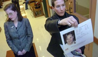 Janet Jenkins, right, of Fair Haven, Vt. who is involved in a same-sex custody battle with Virginia mother Lisa Miller, holds up a photo of her daughter, Isabella, for television cameras after a family court judge in Rutland, Vt., issued an arrest warrant for Lisa Miller on Tuesday, Feb. 23, 2010. A woman who allegedly fled the United States for Nicaragua in 2009 rather than share custody of her child with her former same-sex partner has been arrested in Miami. Federal court records say that Lisa Miller was taken into federal custody Jan. 27. She is awaiting transfer to Buffalo, New York, where she was indicted in 2014 on international parental kidnapping charges.  (Vyto Starinskas/Rutland Herald via AP, file)