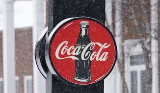 A Coca-Cola sign hangs outside a Coca-Cola distributor, Tuesday, Feb. 9, 2021, in Bedford, Ohio. The resurgent coronavirus slowed Coca-Cola's recovery in the fourth quarter, and the company said the slump has continued through the first months of this year. (AP Photo/Tony Dejak)