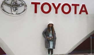 A woman stands at Toyota gallery in Tokyo on Jan. 15, 2020. Toyota reported a 50% jump in its October to December profit Wednesday, Feb. 10, 2021, underlining a solid recovery at the Japanese automaker from the damage of the coronavirus pandemic. (AP Photo/Koji Sasahara)