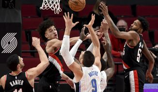 Orlando Magic center Nikola Vucevic, center, battles for a rebound with Portland Trail Blazers center Enes Kanter, left, guard CJ Elleby, middle, and forward Derrick Jones Jr., right, during the first half of an NBA basketball game in Portland, Ore., Tuesday, Feb. 9, 2021. (AP Photo/Steve Dykes)