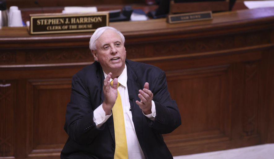 West Virginia Governor Jim Justice applauds the West Virginia Supreme Court Justices during the State of the State Address in the House Chambers of the West Virginia State Capitol Building in Charleston, W.Va., on Wednesday, Feb. 10, 2021. (AP Photo/Chris Jackson)