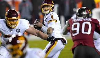 FILE - Washington Football Team quarterback Taylor Heinicke (4) looks to pass against the Tampa Bay Buccaneers during the second half of an NFL wild-card playoff football game in Landover, Md., in this , Saturday, Jan. 9, 2021, file photo. Washington re-signed quarterback Taylor Heinicke to an $8.75 million, two-year contract, Wednesday, Feb. 10, 2021. (AP Photo/Julio Cortez, File)