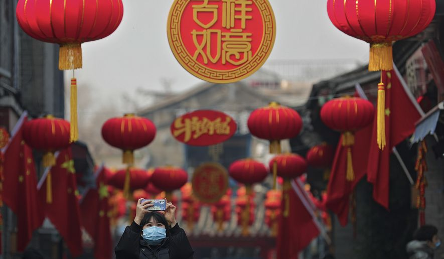 A woman wearing a face mask to help curb the spread of the coronavirus takes a photo under red lanterns decorated along an alley in celebration of the Lunar New Year in Beijing, Thursday, Feb. 11, 2021. China appeared to be on pace for a slower than normal Lunar New Year travel rush this year after authorities discouraged people from traveling over the holiday to help maintain the nation's control over the ongoing COVID-19 pandemic. (AP Photo/Andy Wong)