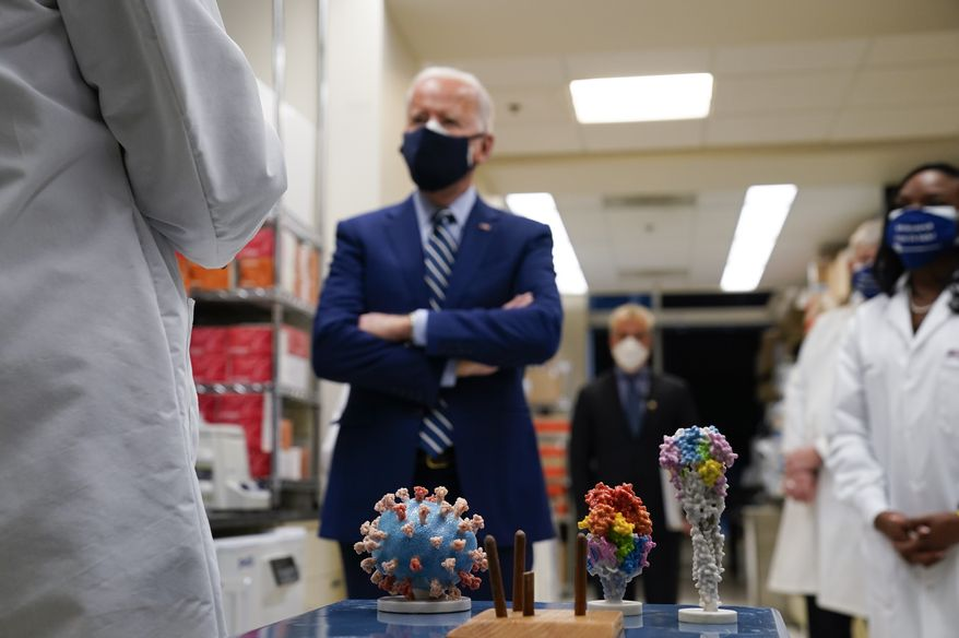 With a model of the COVID-19 virus displayed, President Biden listens as Dr. Barney Graham, left, speaks during a visit at the Viral Pathogenesis Laboratory at the National Institutes of Health (NIH), Thursday, Feb. 11, 2021, in Bethesda, Md. Kizzmekia Corbett, an immunologist with the Vaccine Research Center at the NIH, listens at right. (AP Photo/Evan Vucci)