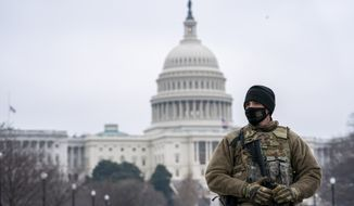 Member of the national guard patrol the area outside of the U.S. Capitol on the third day of the impeachment trial of former President Donald Trump at Capitol Hill, in Washington, Thursday, Feb. 11, 2021. (AP Photo/Jose Luis Magana)