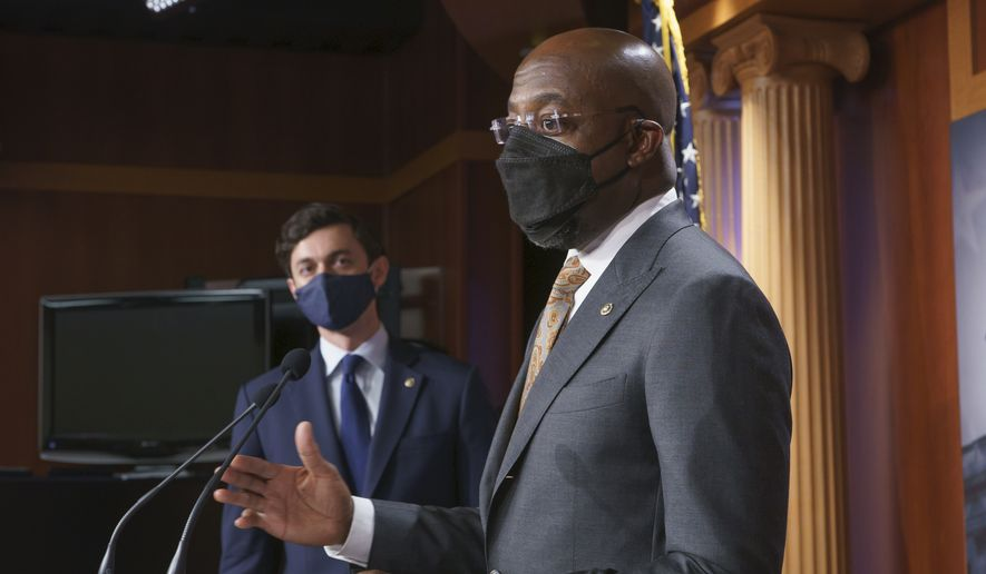 Sen. Raphael Warnock, D-Ga., joined at left by Sen. Jon Ossoff, D-Ga., speaks during a news conference with Senate Majority Leader Chuck Schumer, D-N.Y., about the COVID relief bill, at the Capitol in Washington, Thursday, Feb. 11, 2021. (AP Photo/J. Scott Applewhite)