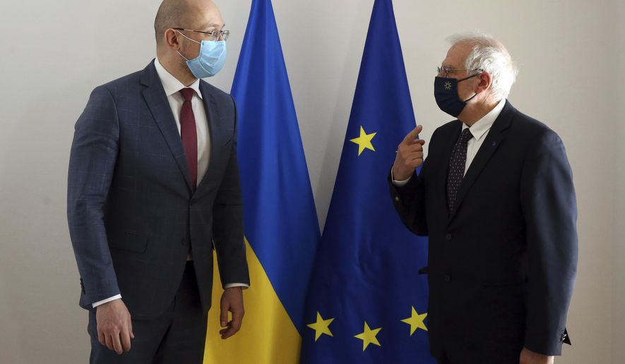 European Union foreign policy chief Josep Borrell, right, talks to Ukraine's Prime Minister Denys Shmyhal as they arrive for an EU-Ukraine Association Council at the European Council headquarters in Brussels, Thursday, Feb. 11, 2021. (Francois Walschaerts, Pool Photo via AP)