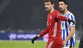 Bayern's Thomas Mueller stands next to Berlin's Sami Khedira, right, during the German Bundesliga soccer match between Hertha BSC Berlin and FC Bayern Munich in Berlin, Germany, Friday, Feb. 5, 2021. (John MacDougall/pool via AP)
