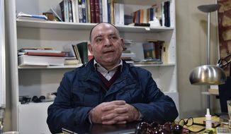 This photo provided by Monika Borgmann shows her husband, Lokman Slim, a well-known Lebanese publisher and vocal critic of Hezbollah, the Lebanese Shiite Muslim group, at his desk in the southern Beirut suburb of Dahiyeh, Lebanon, Jan. 5, 2017. Slim was killed Thursday, Feb. 4, 2021. Borgmann said she is discussing with lawyers and friends how to push for an international investigation into her husband's murder. (Lokman Slim family via AP)