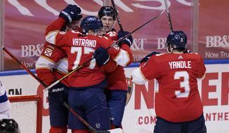 Florida Panthers teammates congratulate center Frank Vatrano (77) after Vatrano scored a goal during the first period at an NHL hockey game against the Tampa Bay Lightning, Thursday, Feb. 11, 2021, in Sunrise, Fla. (AP Photo/Marta Lavandier)